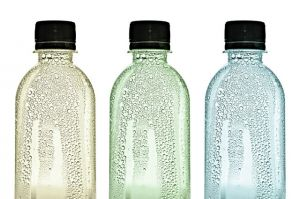 Three plastic bottles with water drops on skins