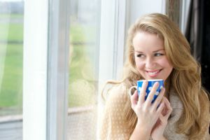Smiling young lady holding cup of tea