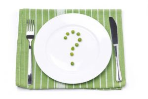 empty plate with green peas in the shape of a question mark