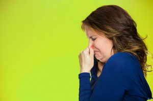 woman covers pinches her nose something stinks