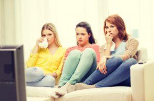 three sad teenage girl watching tv at home