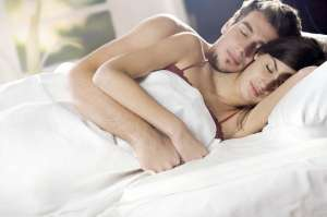 Couple sleeping and hugging on the bed in bedroom