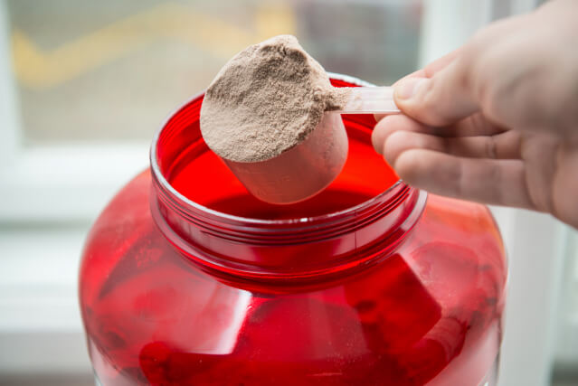 Man taking protein from container by the scoop.