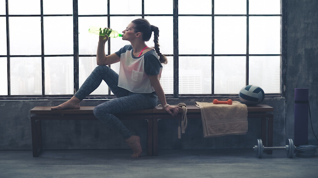 Fit woman in profile sitting on bench in loft gym drinking water