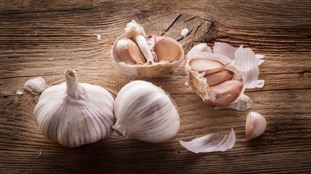 Garlic bulbs and cloves on wooden table, closeup