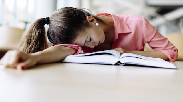 Beautiful pretty woman fallen asleep while studying