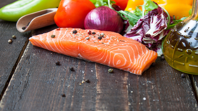 fresh salmon with vegetables on a wooden table