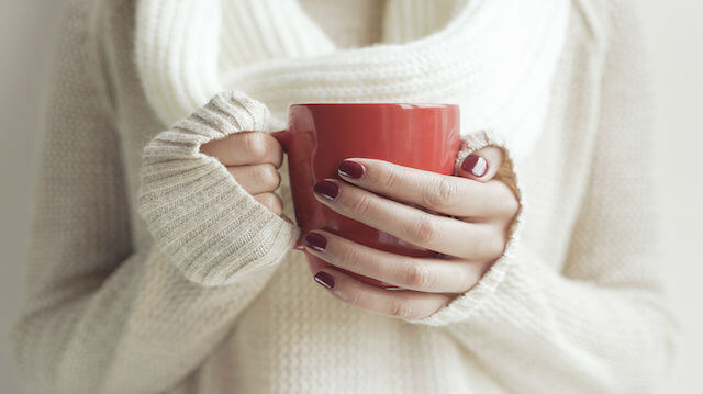 Cup of tea or coffee in female hands.