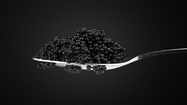 Black caviar in metal teaspoon. Macro photo on dark background