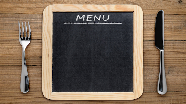 Fork, knife and blackboard menu on wooden background