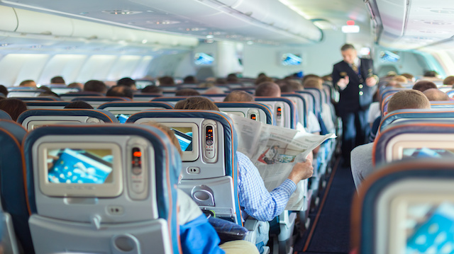 Steward and passengers on commercial airplane.