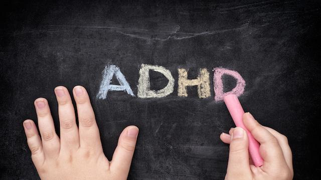 Child writing ADHD on blackboard