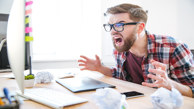 Mad agressive man designer looking on monitor and shouting