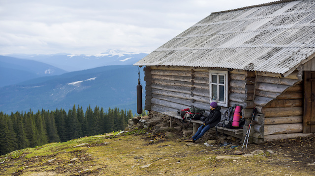 hiker sitting near the wooden cabine in mountains
