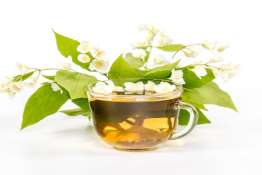isolated transparent cup of tea with jasmine flowers.