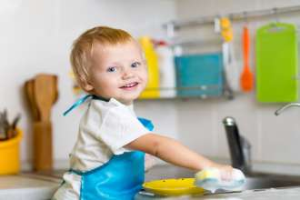 Toddler child washing dishes in kitchen. Little boy having fun with helping to his mother with housework.