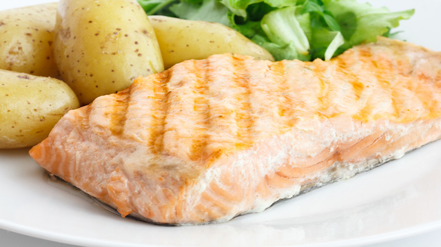 Grilled fillet of salmon on plate with green salad and potatoes.
