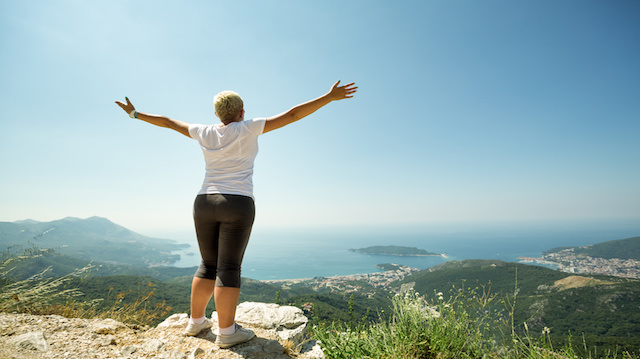 Woman with raised up hands enjoying sunny day