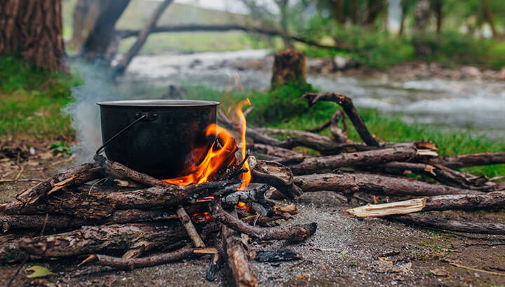 Distill saltwater with a cooking pot over a fire.